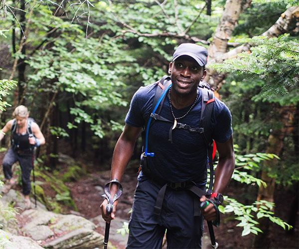 A man hikes through a lush forest.