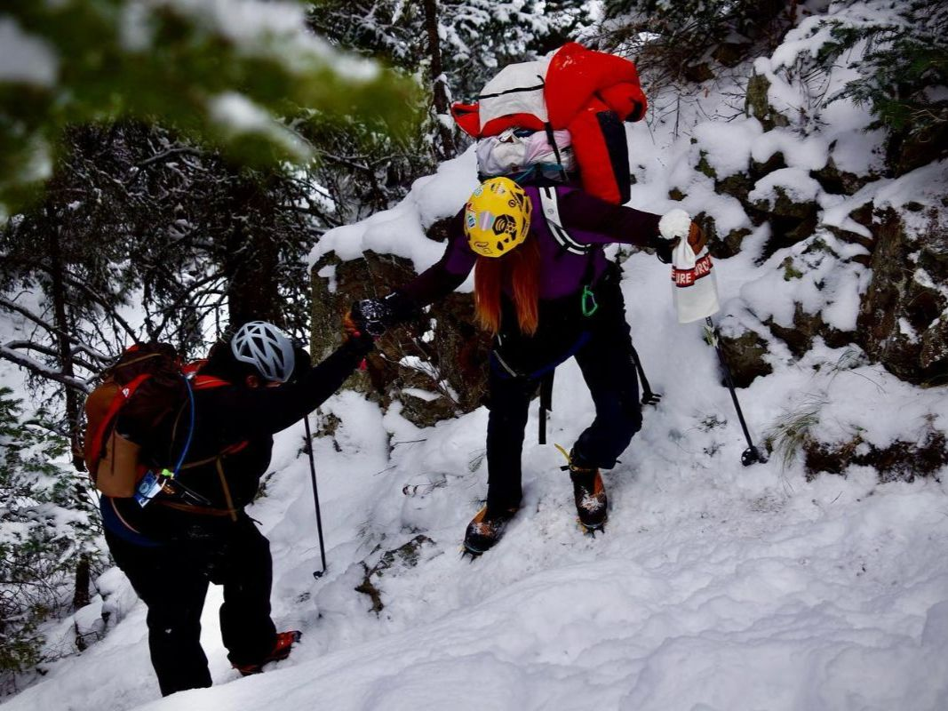 two people backpacking in the snow, climbing up a mountain helping one another. The and rocks are covered in fresh white fluffy snow
