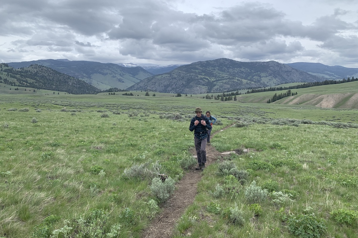 two people hiking on a trail with green all around and large mountains in the background its an overcast day