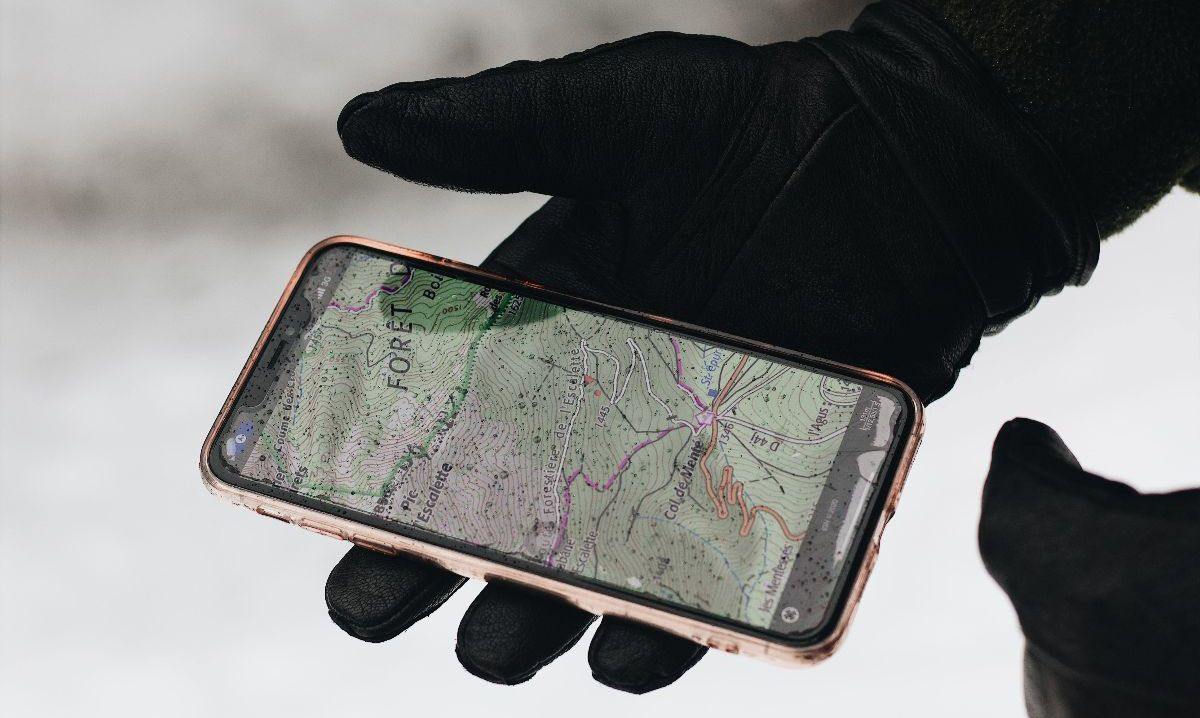 a person holding a phone with map app up