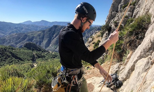 a person wearing a black shirt in the mountains about to climb as a rope is in his hand