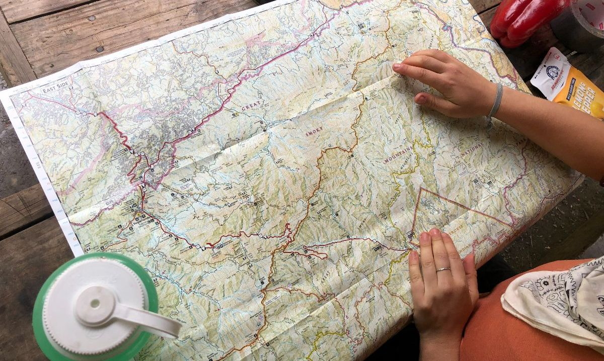 a open map on a table with someone looking at it.